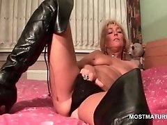 Mature blonde tramp rubs her wet pussy in bed